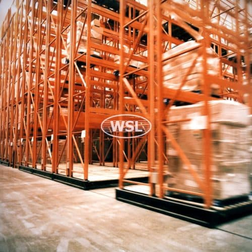 Long exposure of busy warehouse with Powered mobile racking in orange