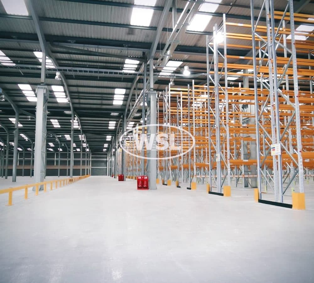 Wide angle view of Pallet racking and warehouse lighting. Racking finished in Orange and Silver